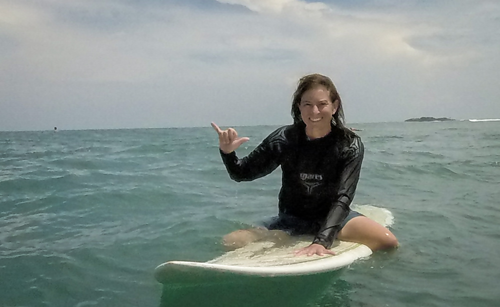 Surfer girl doing the shaka and enjoying a great day surfing in paradise