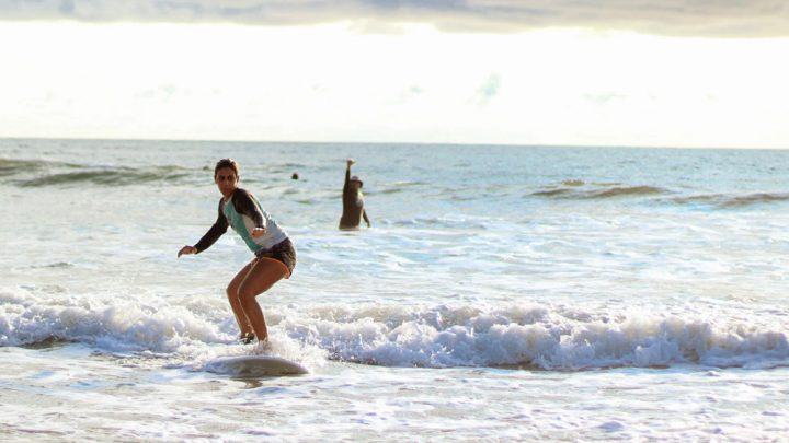 Catching the first wave, girl learning to surf in Santa Teresa