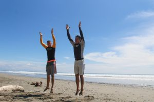 SURF and surf coach warming up before surf sesion beautiful sunny beach day in Montezuma Surf School