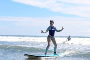 Beginner surf girl catching waves at Montezuma Surf School