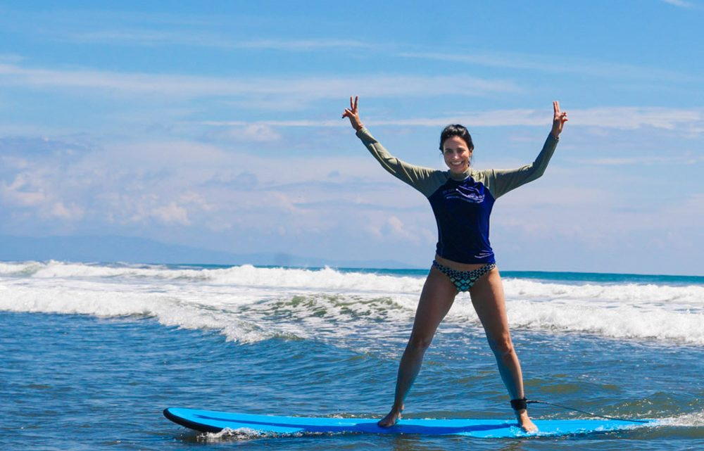 Happy surfing girl learn to surf in Montezuma best surf school Costa Rica