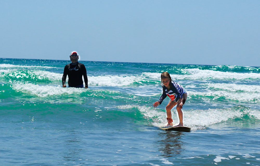 Little girl learn to surf lessons with safety and fun in Montezuma best surf school