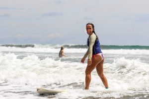 Woman learning to surf in sunny beach Montezuma Costa Rica