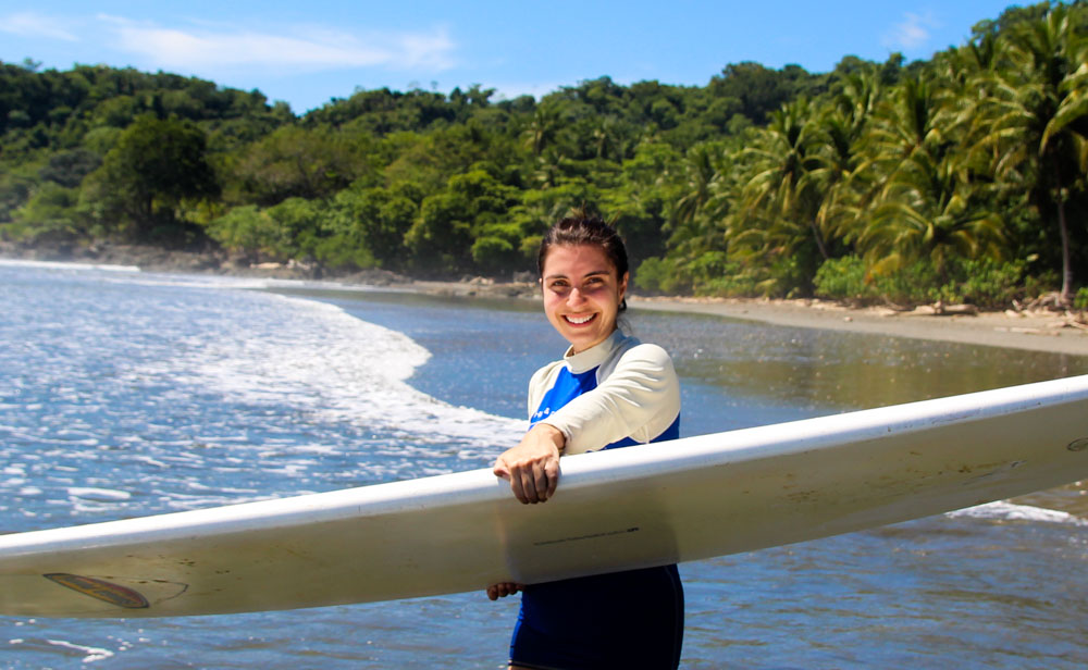 Happy surfer girl at Playa Grande beautiful beach in a sunny day