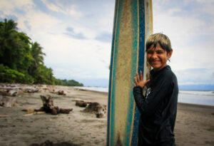 11 year-old surfer boy with his surfboard at Montezuma, Costa Rica tropical beach