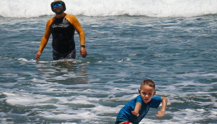 Little surfer boy catching waves on a beautiful sunny beach day