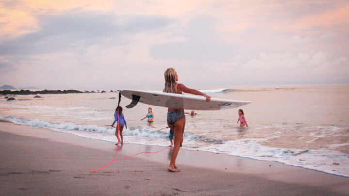 Surfer girl and kids playing at the beach with great waves in the back